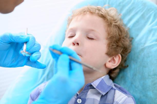 Close up of boy having his teeth examined by a dentist picture id696296504?b=1&k=6&m=696296504&s=612x612&w=0&h=8egwi6ugrtwiglnxw4dtq5d4n9 9bfayrnjcd5s rxi=