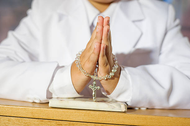 close up of boy praying - communion stock photos and pictures