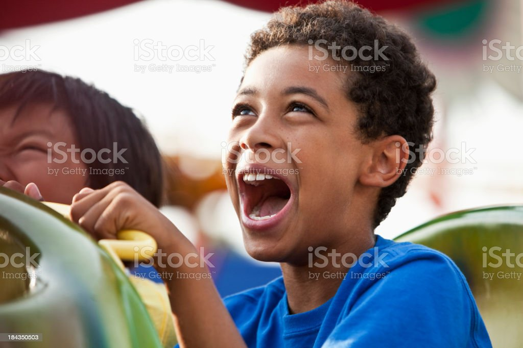 Close up of boy screaming on roller coaster stock photo
