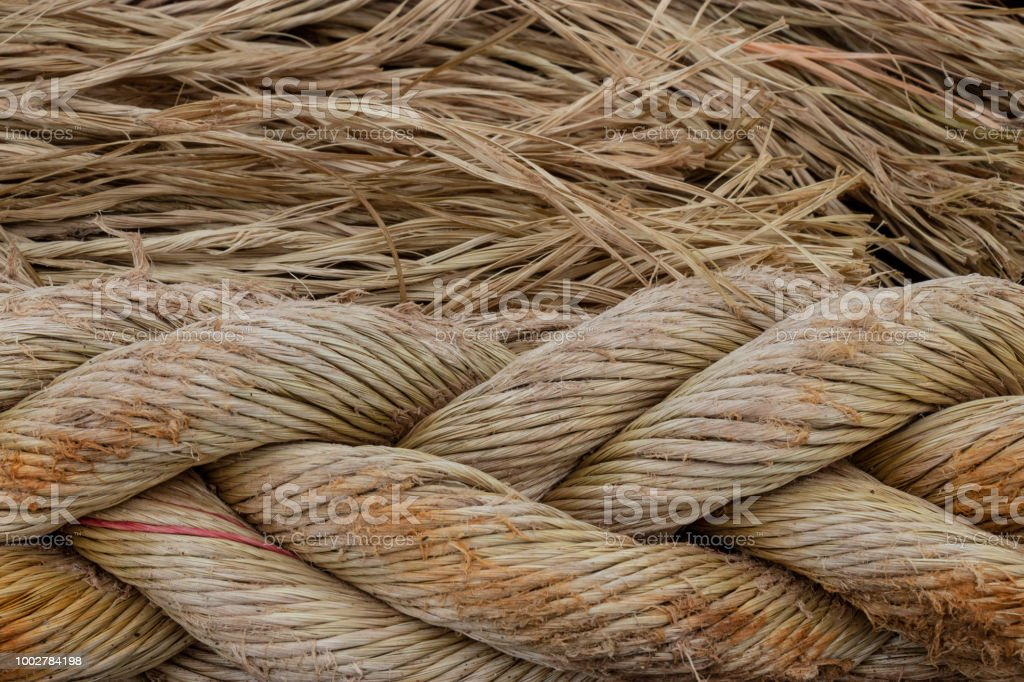 A close up of braided natural fiber brown rope with unraveled strands. stock photo