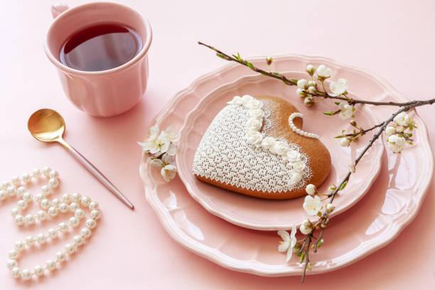 Feche acima da filial do copo de florescência da cereja do chá, colar da pérola, Gingerbread no fundo cor-de-rosa dos doces pastel - foto de acervo