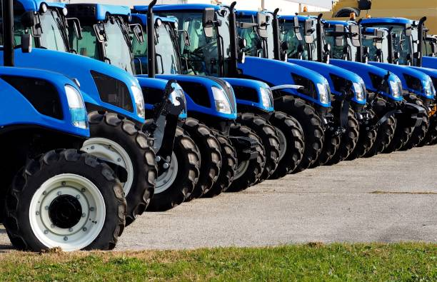Close up of brand new blue tractors,  side by side, in a long line Close up of brand new blue tractors,  side by side, in a long line . agricultural machinery stock pictures, royalty-free photos & images