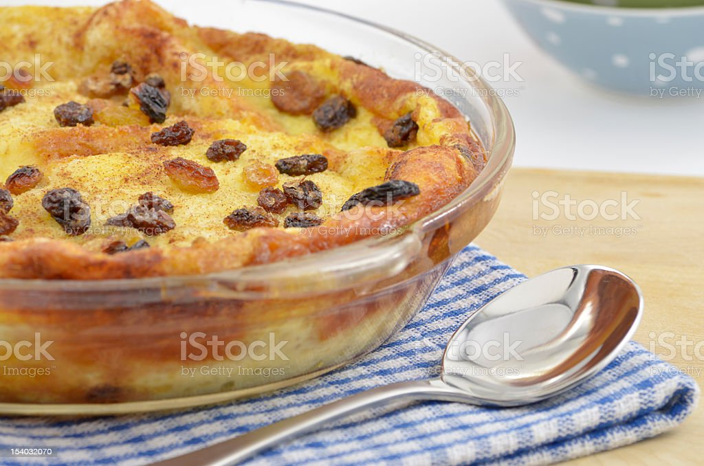 Close up of bread pudding with raisins and a spoon on napkin stock photo