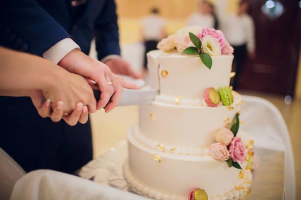 Nahaufnahme von Braut und Bräutigam schneiden Hochzeitstorte. – Foto