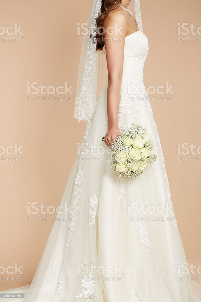 Close up of bride in wedding dress holding bouquet stock photo