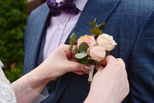 Close up of bride putting on boutonniere to the groom's tux, copy space. Wedding couple in love, newlyweds. Wedding concept