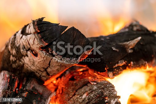 Close up of brightly burning wooden logs with yellow hot flames of fire at night.