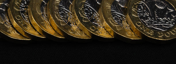 close up of British pound coins in a row on black background, web banner stock photo