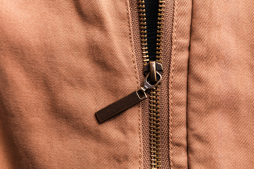 Close up of brown jeans zipper