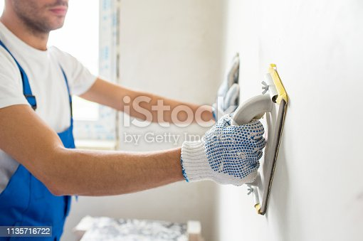 building, profession and people concept - close up of male builder sanding wall indoors