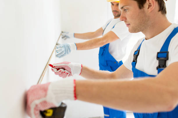 close up of builders measuring wall with tape stock photo