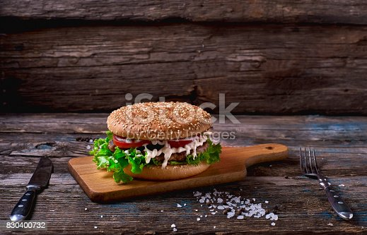 Close Up of Burger Piled High with Fresh Toppings on Whole Grain Artisan Bun, on Rustic Wooden Surface with Dark Background and Copy Space, Horizontal.