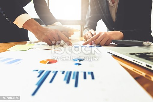 istock Close up of business man hand pointing at business document on financial paper on wooden desk during discussion at meeting. Group support concept. 897853130