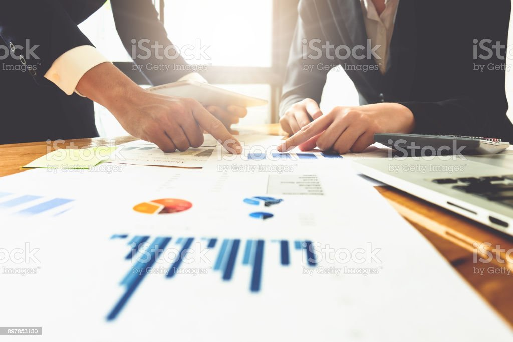 Close up of business man hand pointing at business document on financial paper on wooden desk during discussion at meeting. Group support concept. stock photo
