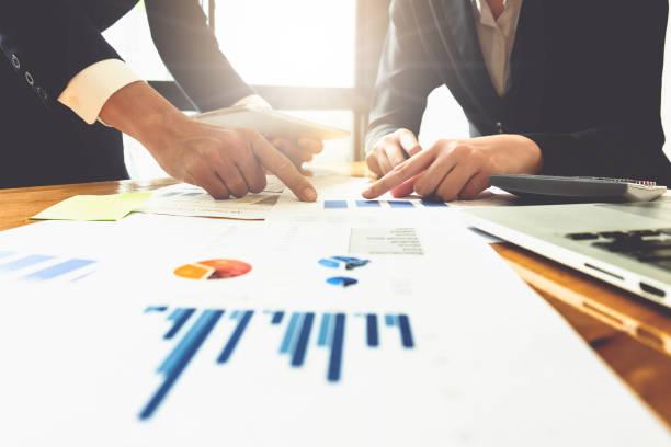 会議での議論の間に金融紙木製机の上でビジネス ドキュメントを指すビジネス人間手のクローズ アップ。グループ サポート概念。 - 金融と経済 ストックフォトと画像