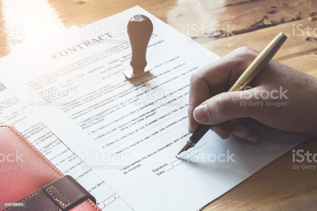 Close up of Business man pointing and signing agreement contract for buying house. Bank manager concept. stock photo