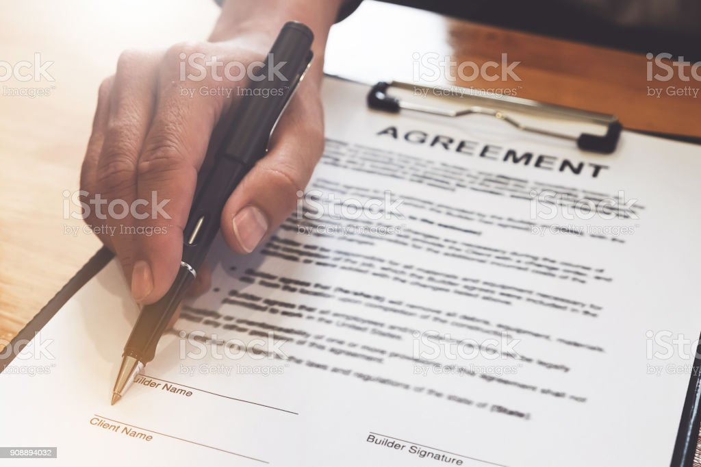 Close up of Business man pointing and signing agreement for buying house. Bank manager concept. stock photo
