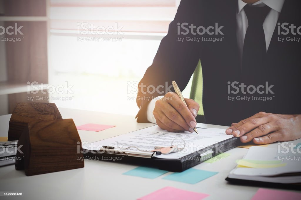 Close up of Business man signing agreement for buying house. Bank manager concept. stock photo