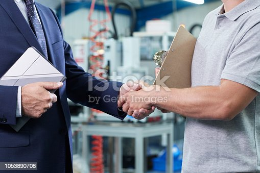 Close Up Of Business Owner With Digital Tablet In Factory Shaking Hands With Engineer