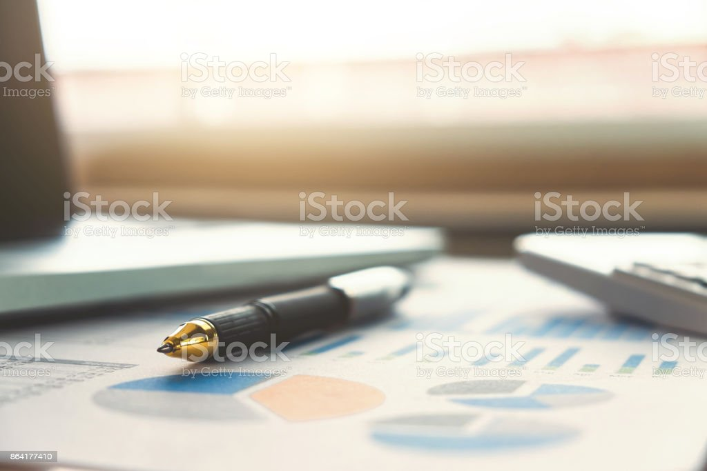 Close up of business pen and white calculator on financial graph data with laptop. finance, saving, investment, business and banking concept royalty-free stock photo