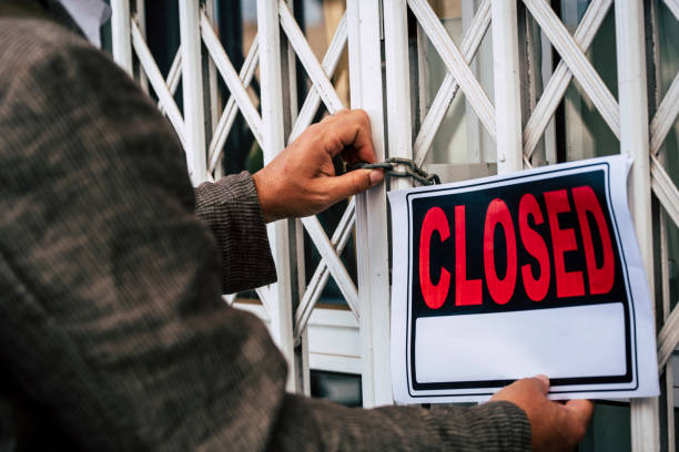 Close up of business people man with closed sign outside the shop and store close - crisis and bad economy situation - no money bankrupt economy lockdown stock photo