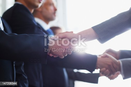 istock Close up of business people shaking hands in a row 147205344