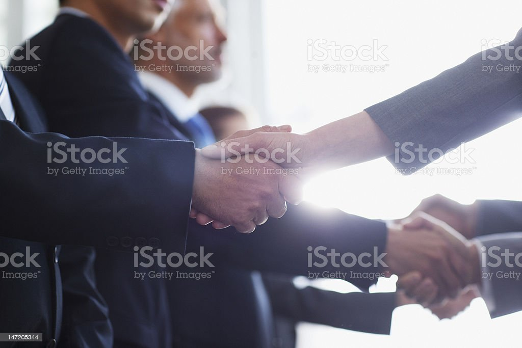 Close up of business people shaking hands in a row stock photo
