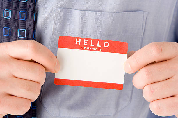 close up of businessman attaching name tag - identity stock photos and pictures