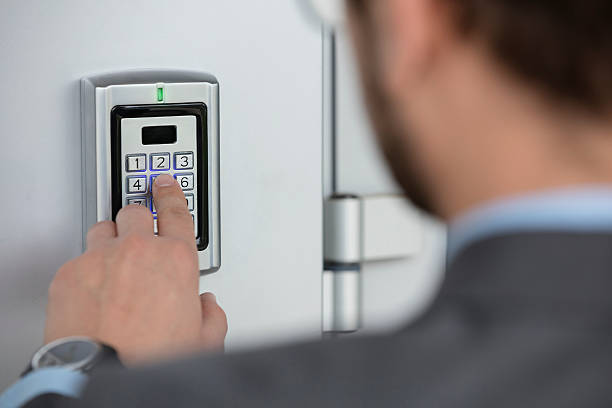 Close up of businessman hand entering security system code stock photo