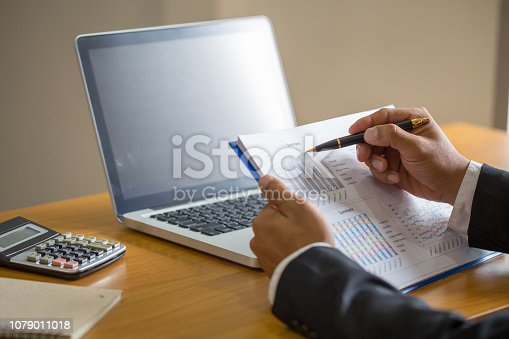 801895196istockphoto close up of businessman hand working on laptop computer with financial business graph information,  analyzing investment charts. 1079011018