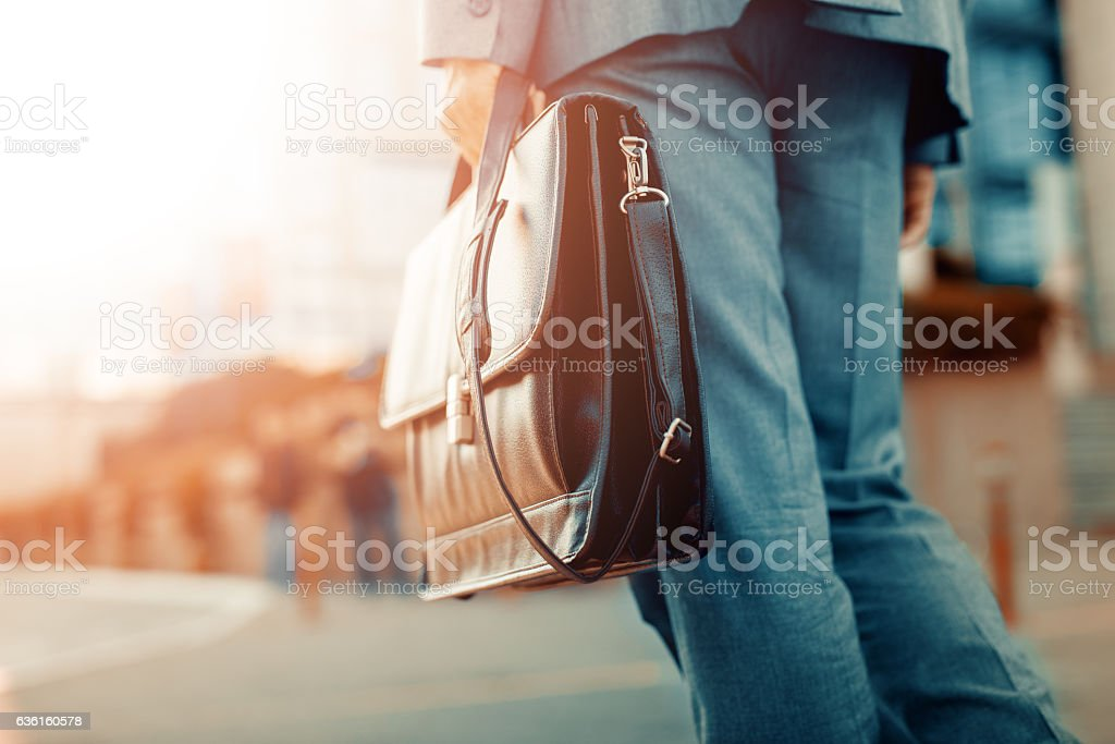 Close up of businessman holding a briefcase Cropped view of businessman holding a briefcase outdoors Adult Stock Photo