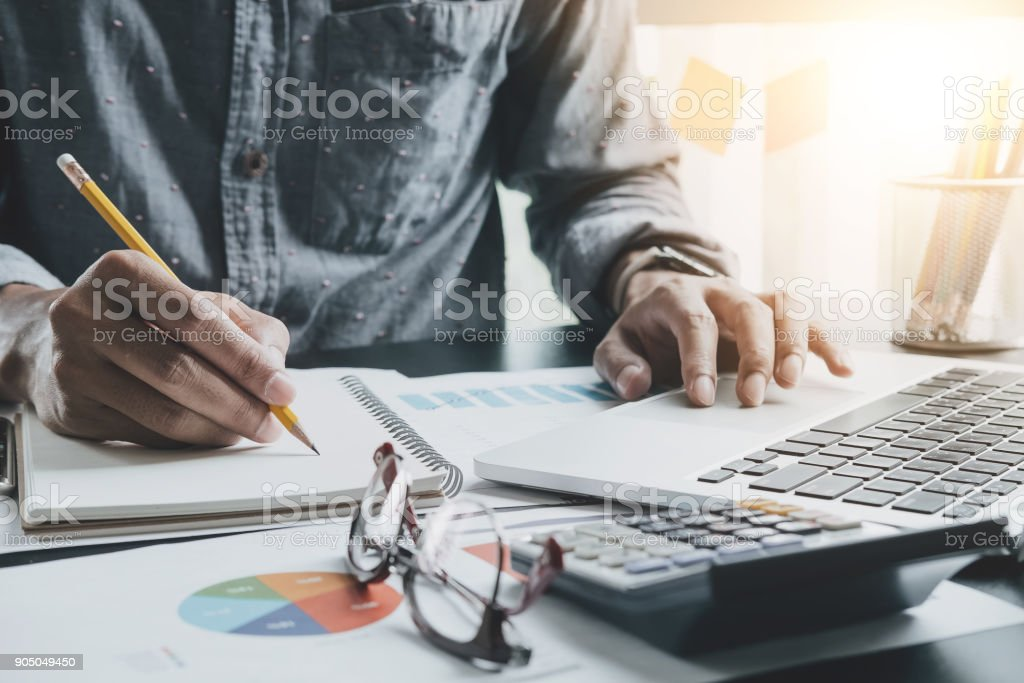 Close up of businessman or accountant hand holding pen working making notes and using laptop computer to calculate business data, accountancy document at his office, business accounting concept foto stock royalty-free