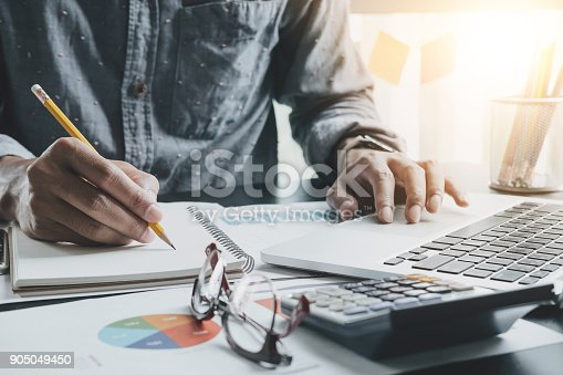 istock Close up of businessman or accountant hand holding pen working making notes and using laptop computer to calculate business data, accountancy document at his office, business accounting concept 905049450