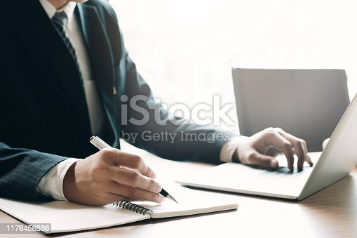 897852992istockphoto Close up of businessman or accountant hand holding pen working on laptop computer for calculate business data, accountancy document and calculator at office, business concept 1176456886