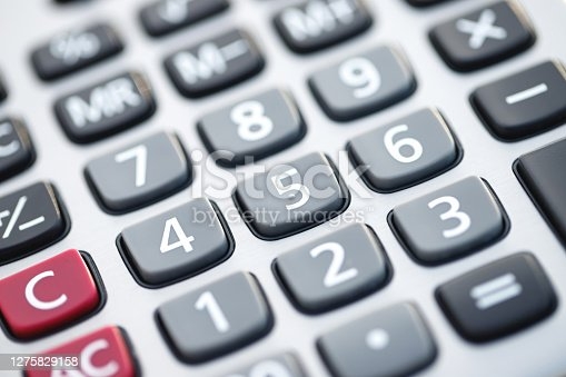 Close up of businessman or accountant hand holding pen working on calculator