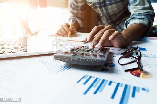 istock Close up of businessman or accountant hand holding pen working on calculator and laptop computer to calculate business data during make note at notepad, accountancy document at office, business financial concept 865226698