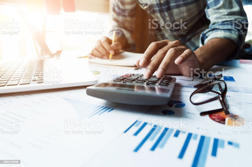 Close up of businessman or accountant hand holding pen working on calculator and laptop computer to calculate business data during make note at notepad, accountancy document at office, business financial concept – zdjęcie