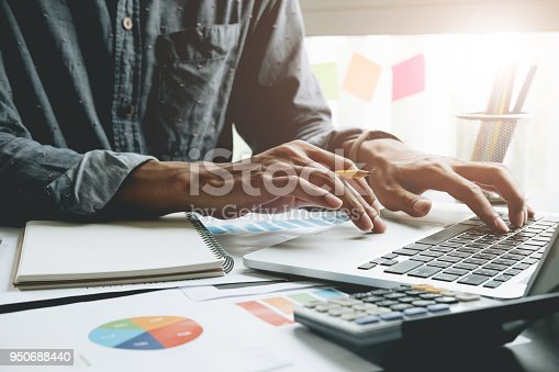 istock Close up of businessman or accountant hand holding pen working on laptop computer for calculate business data, accountancy document and calculator at office, business concept 950688440