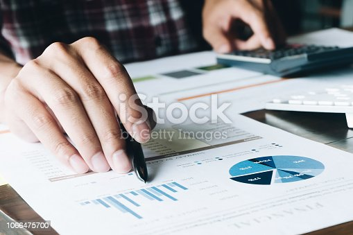 897852992istockphoto Close up of businessman or accountant hand holding pen working on calculator to calculate business data, accountancy document and laptop computer at office, business concept 1066475700