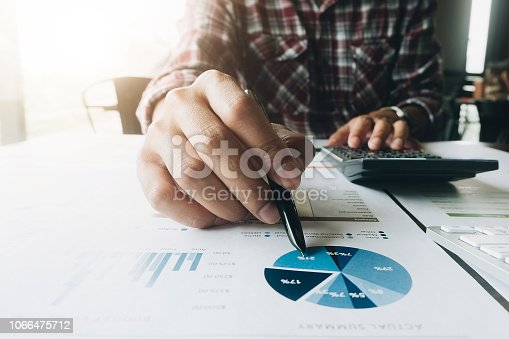 897852992istockphoto Close up of businessman or accountant hand holding pen working on calculator to calculate business data, accountancy document and laptop computer at office, business concept 1066475712