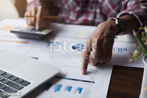 897852992istockphoto Close up of businessman or accountant hand holding pen working on calculator to calculate business data, accountancy document and laptop computer at office, business concept 1078469764
