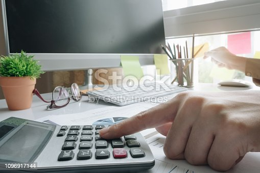 897852992istockphoto Close up of businessman or accountant hand holding pen working on calculator to calculate business data, accountancy document and laptop computer at office, business concept - Image 1096917144