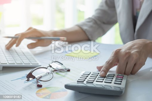 897852992istockphoto Close up of businessman or accountant hand holding pen working on calculator to calculate business data, accountancy document and laptop computer at office, business concept - Image 1096919182