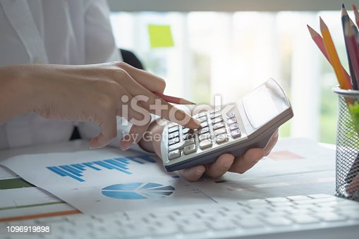 897852992istockphoto Close up of businessman or accountant hand holding pen working on calculator to calculate business data, accountancy document and laptop computer at office, business concept - Image 1096919898