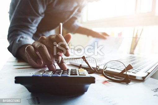 istock Close up of businessman or accountant hand holding pen working on calculator to calculate business data, accountancy document and laptop computer at office, business concept 849802590