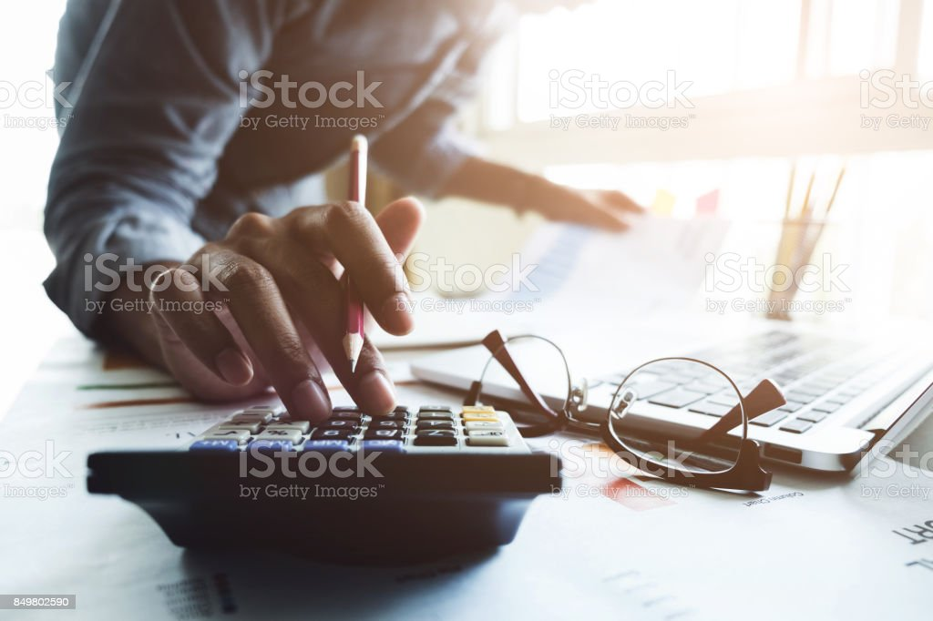 Close up of businessman or accountant hand holding pen working on calculator to calculate business data, accountancy document and laptop computer at office, business concept stock photo