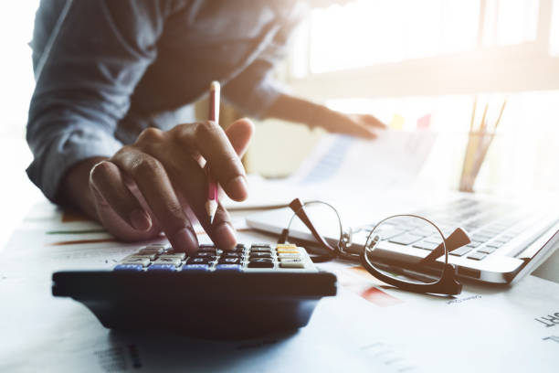 close up of businessman or accountant hand holding pen working on calculator to calculate business data, accountancy document and laptop computer at office, business concept - accountancy stock photos and pictures