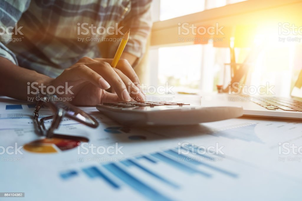 Close up of businessman or accountant hand holding pen working on calculator to calculate business data, accountancy document and laptop computer at office, business concept royalty-free stock photo