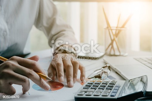 897852992istockphoto Close up of businessman or accountant hand holding pen working on calculator to calculate business data, accountancy document and laptop computer at office, business concept 905049470