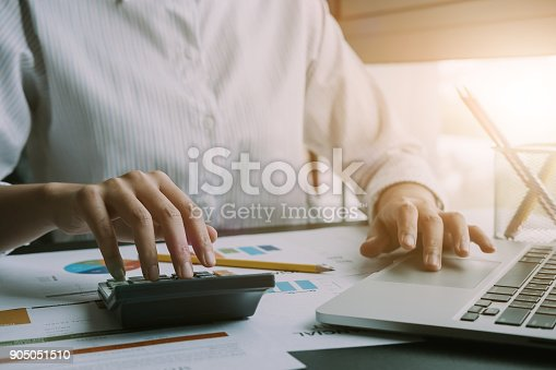 897852992istockphoto Close up of businessman or accountant hand holding pen working on calculator to calculate business data, accountancy document and laptop computer at office, business concept 905051510